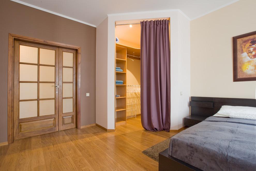 На фото: гардеробная комната среднего размера, унисекс в современном стиле с открытыми фасадами, коричневыми фасадами, полом из ламината и коричневым полом с