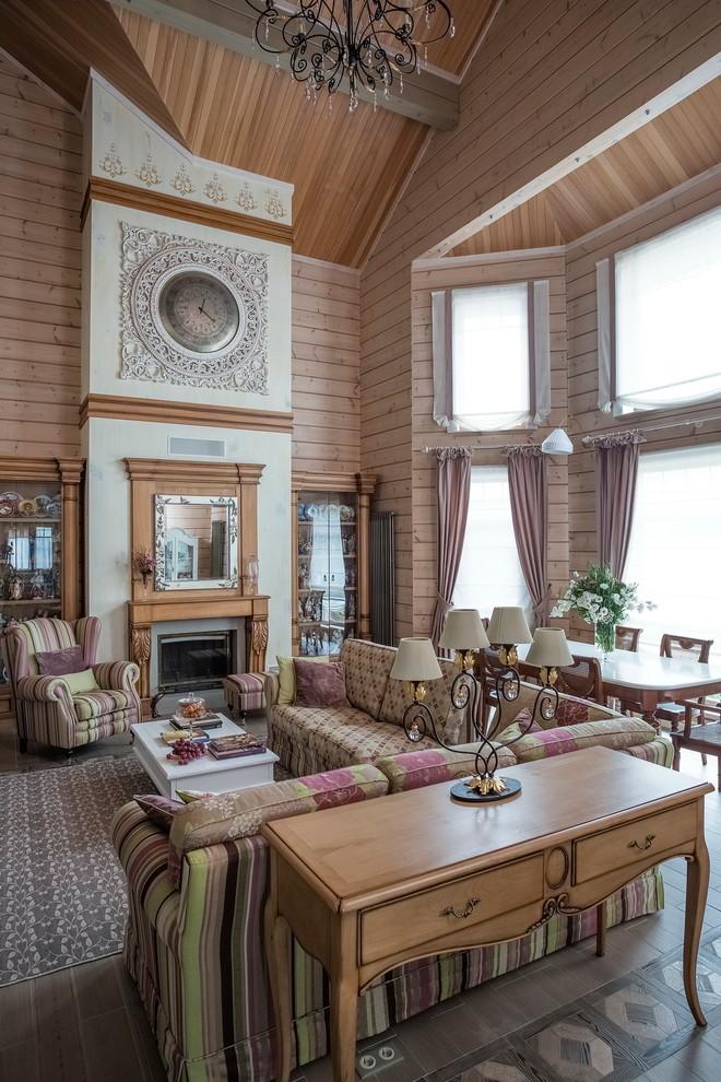 Идея дизайна: большая открытая гостиная комната в стиле фьюжн с полом из керамогранита, стандартным камином, фасадом камина из дерева и мультимедийным центром