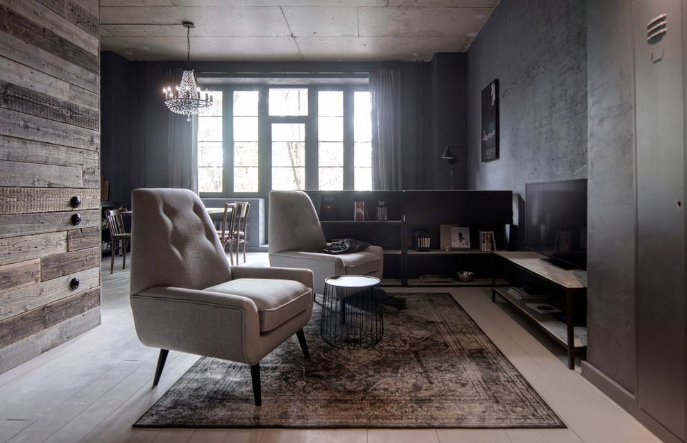 Photo of a small urban open plan living room with a reading nook, painted wood flooring, a freestanding tv, white floors and black walls.
