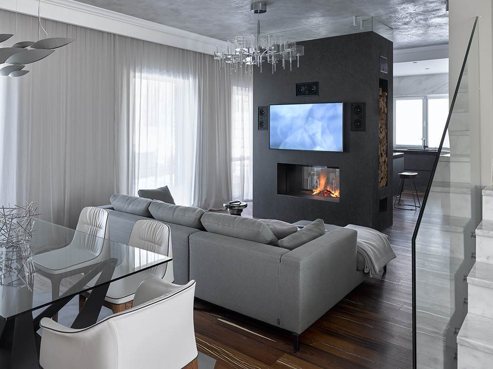 Living room - contemporary formal and open concept dark wood floor and brown floor living room idea in Other with gray walls, a two-sided fireplace and a wall-mounted tv
