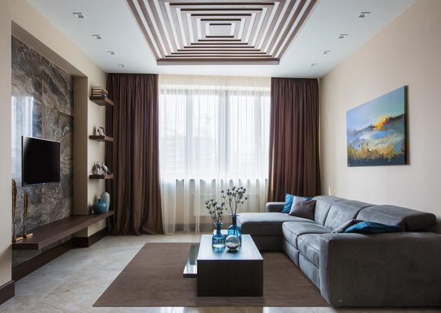 Новые идеи обустройства дома: гостиная комната в современном стиле с бежевыми стенами, телевизором на стене и бежевым полом