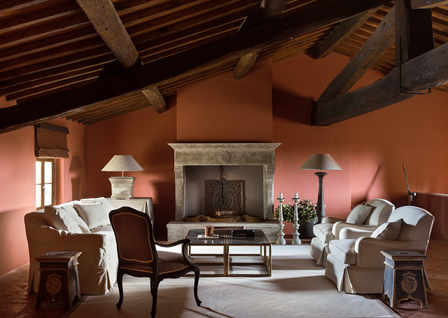 Example of a transitional living room design in Florence with a standard fireplace and orange walls
