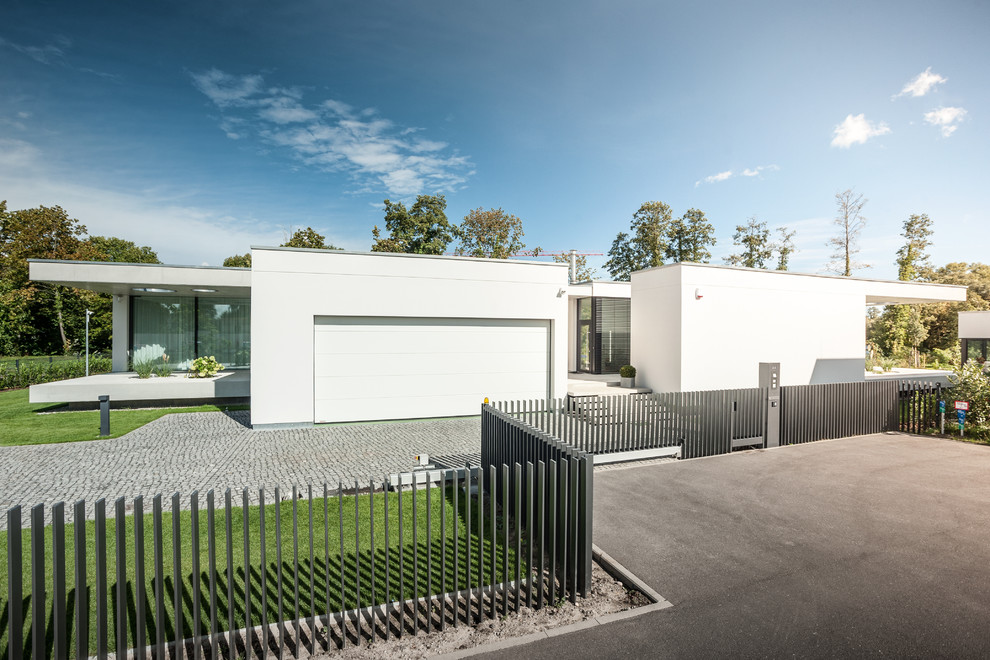 This is an example of a white modern one floor render detached house in Berlin with a flat roof.