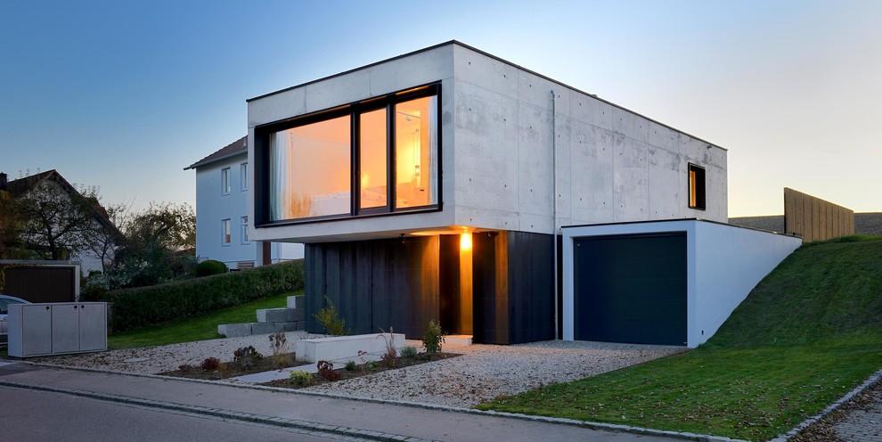 Foto della facciata di una casa piccola grigia contemporanea a due piani con rivestimento in cemento e tetto piano