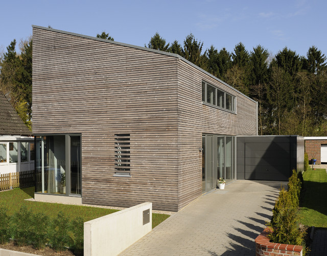 Example of a mid-sized trendy brown two-story wood exterior home design in Berlin with a shed roof