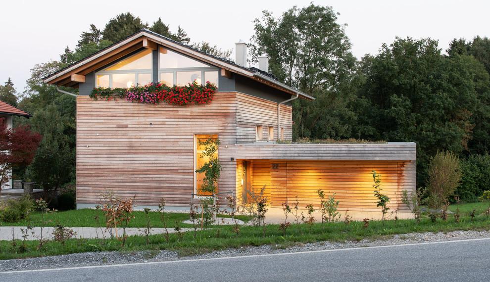 Mittelgroßes, Braunes Nordisches Einfamilienhaus mit Holzfassade, Satteldach und Ziegeldach in München