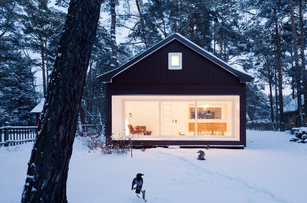 Réalisation d'une façade de maison noire nordique de taille moyenne et à un étage avec un toit à deux pans.
