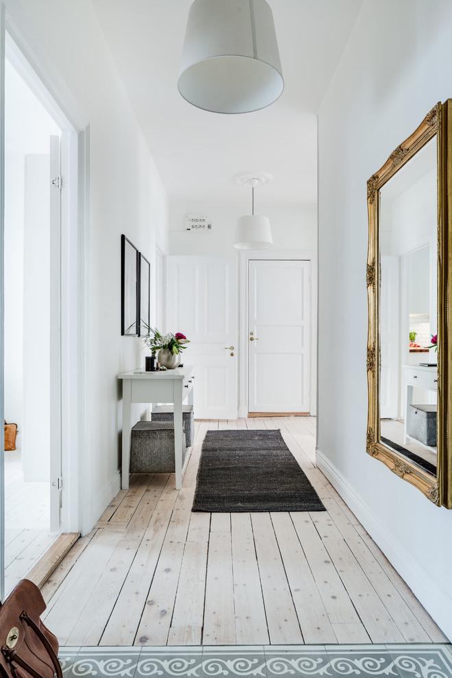 Mid-sized danish light wood floor hallway photo in Gothenburg with white walls