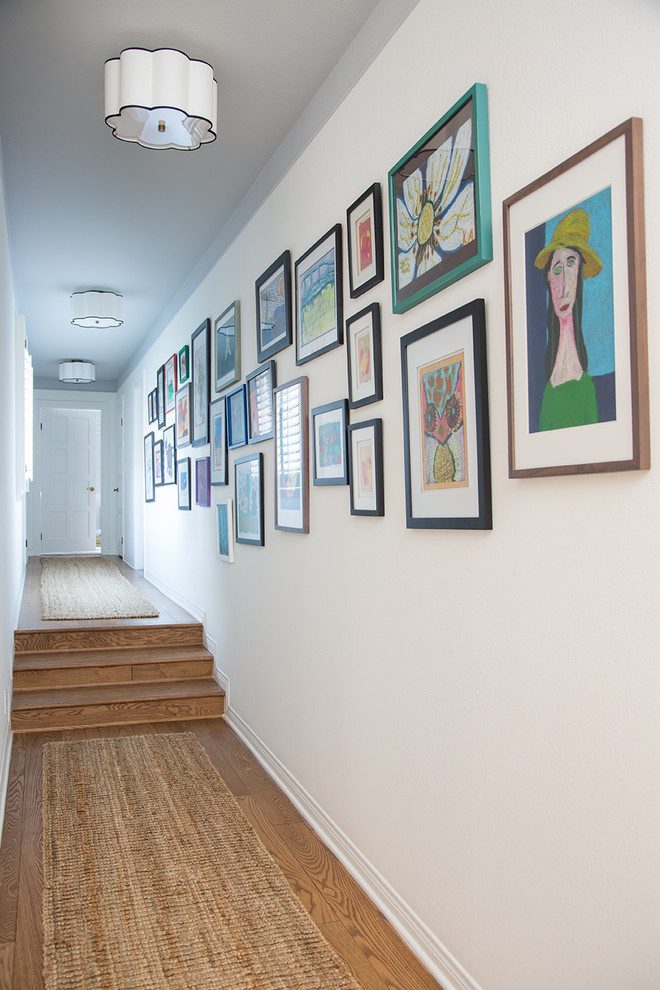Inspiration for a mid-sized eclectic light wood floor and brown floor hallway remodel in Los Angeles with white walls