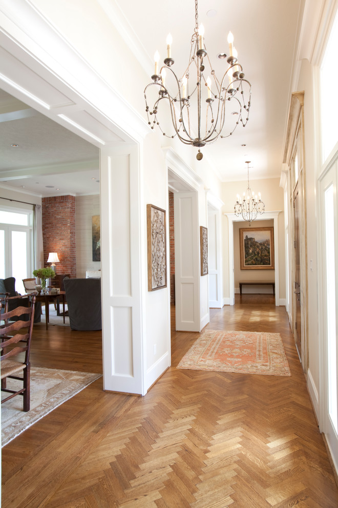 Hallway - large traditional medium tone wood floor hallway idea in Houston with white walls