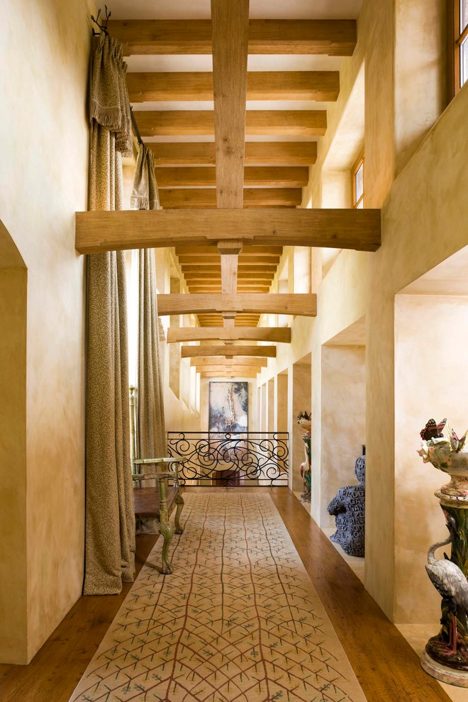 Example of a large tuscan medium tone wood floor hallway design in Denver with beige walls