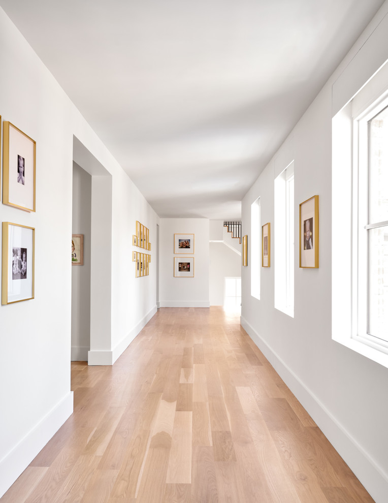 Inspiration for a large transitional medium tone wood floor and brown floor hallway remodel in Dallas with white walls