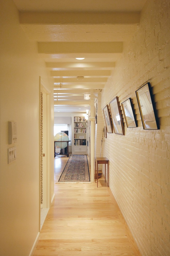 Inspiration for a mid-sized transitional light wood floor and beige floor hallway remodel in Boston with white walls