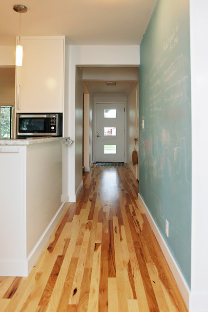 Inspiration for a mid-sized contemporary medium tone wood floor hallway remodel in Minneapolis with white walls