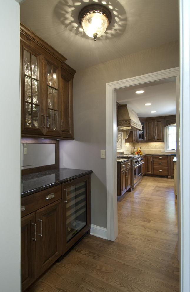 Mid-sized elegant medium tone wood floor hallway photo in Chicago with beige walls