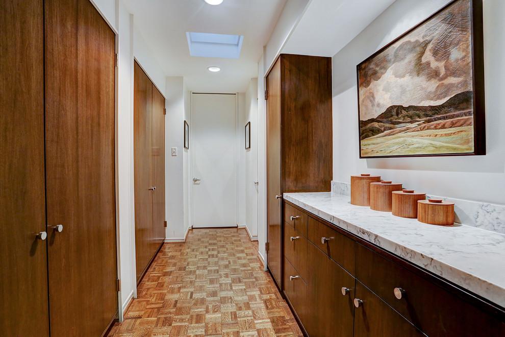 Hallway - mid-sized 1950s medium tone wood floor hallway idea in Houston with white walls