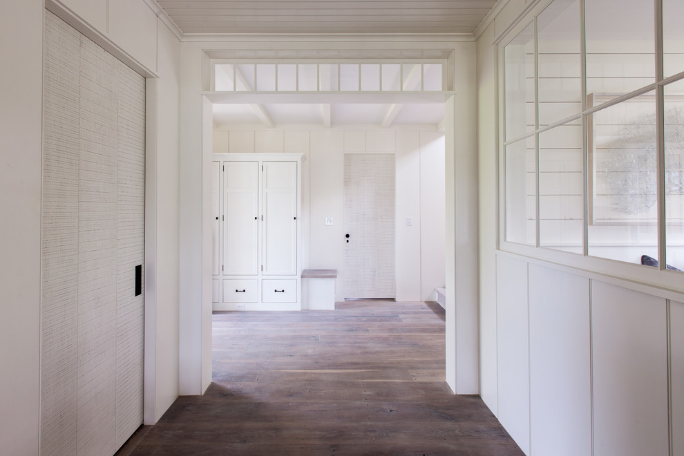 Inspiration for a mid-sized beach style light wood floor hallway remodel in Boston with white walls