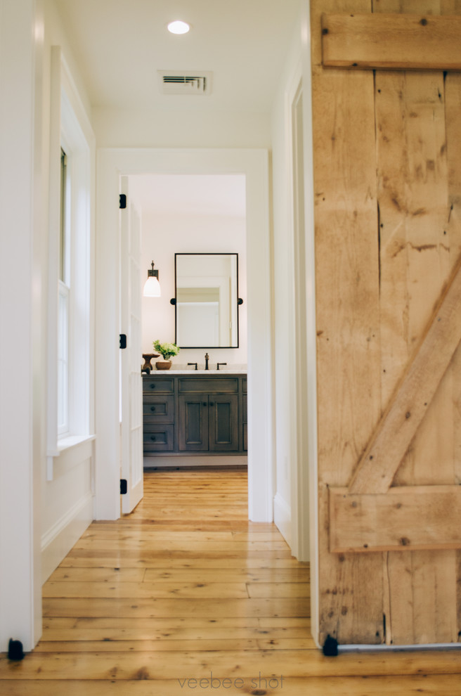 Example of a mid-sized cottage light wood floor hallway design in New York with white walls