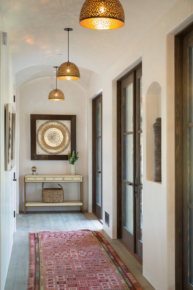 Hallway - mid-sized mediterranean light wood floor and beige floor hallway idea in Los Angeles with beige walls