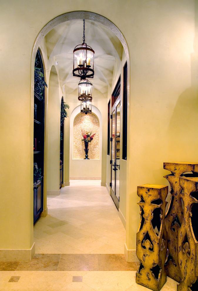 Example of a tuscan beige floor hallway design in Austin with beige walls