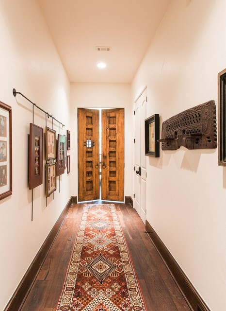 Inspiration for a southwestern dark wood floor hallway remodel in Houston with white walls