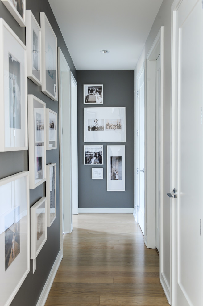 Example of a mid-sized transitional medium tone wood floor hallway design in Vancouver with gray walls