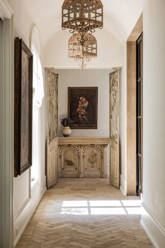 Hallway - mediterranean beige floor hallway idea in Houston with white walls