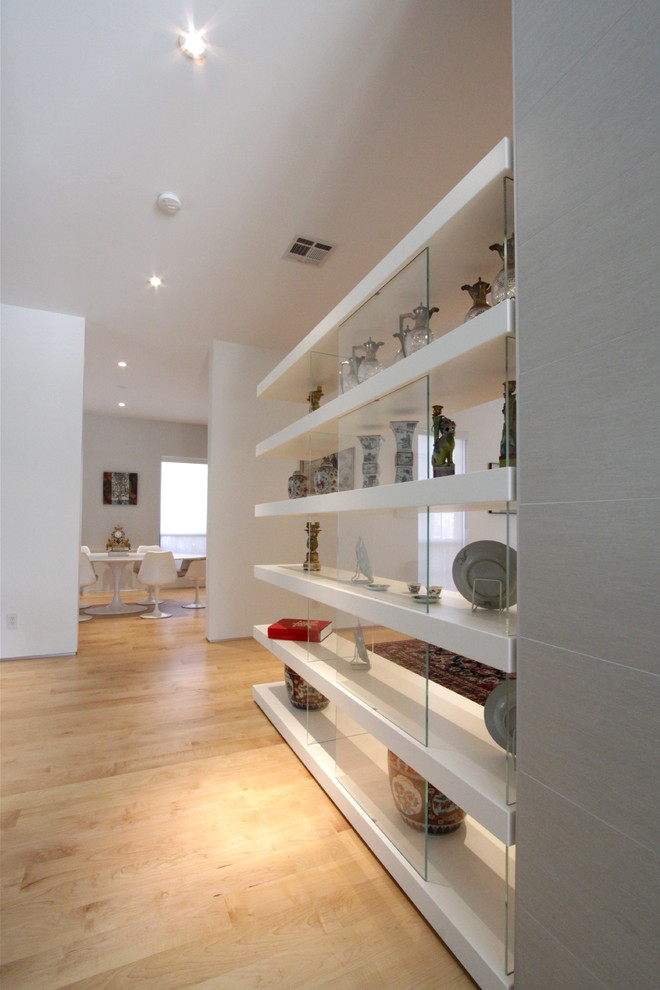 Example of a mid-sized minimalist light wood floor hallway design in Houston with white walls