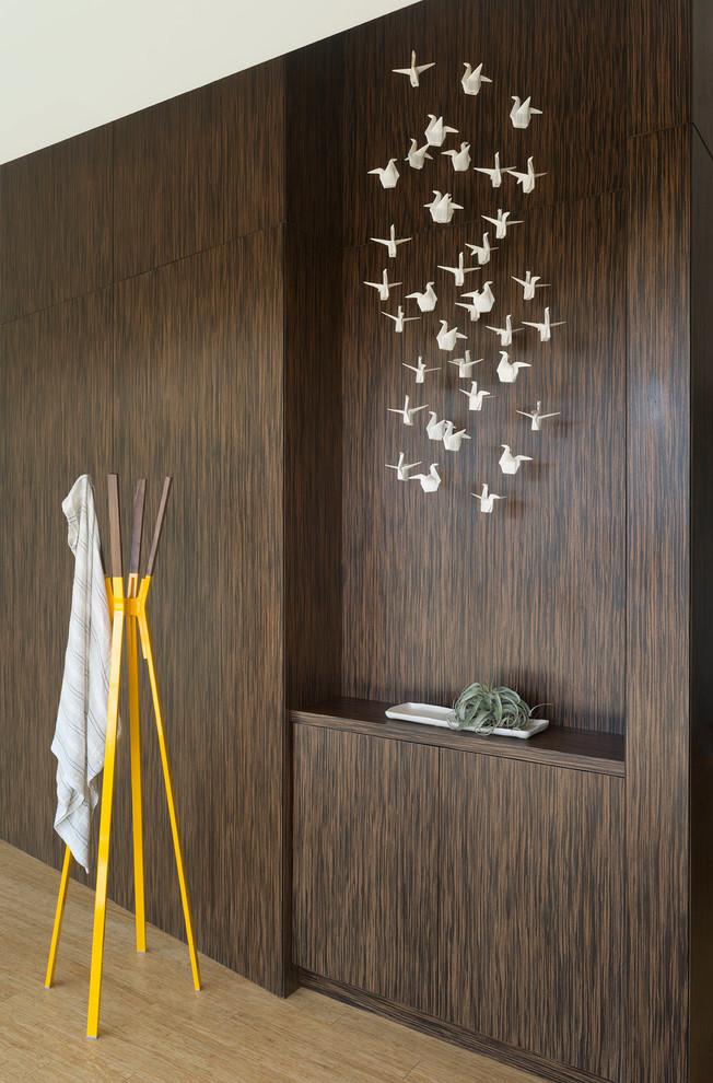 Trendy light wood floor hallway photo in Austin with brown walls