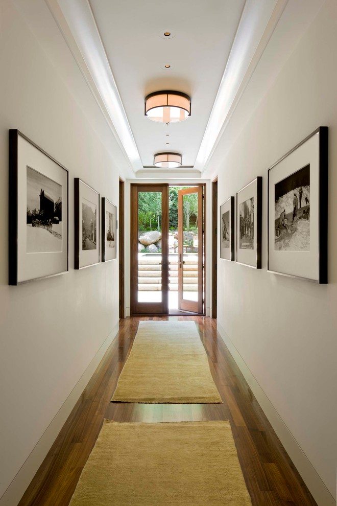Example of a transitional dark wood floor hallway design in Denver with white walls