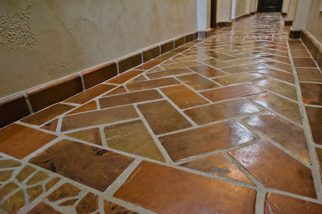 Inspiration For A Large Rustic Terra Cotta Floor Hallway Remodel In Austin With Beige Walls