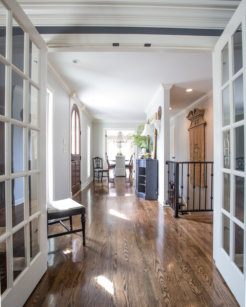 Inspiration for a large timeless medium tone wood floor and brown floor hallway remodel in Other with white walls