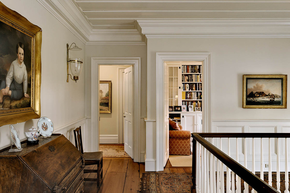 Inspiration for a timeless medium tone wood floor and brown floor hallway remodel in New York with white walls