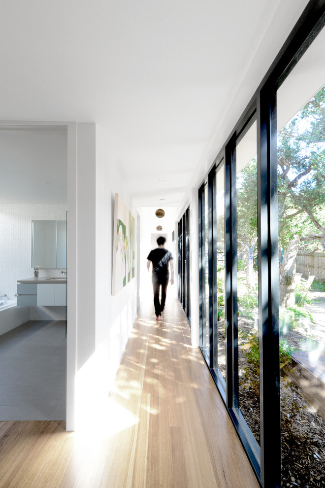Inspiration for a modern light wood floor and beige floor hallway remodel in Melbourne with white walls