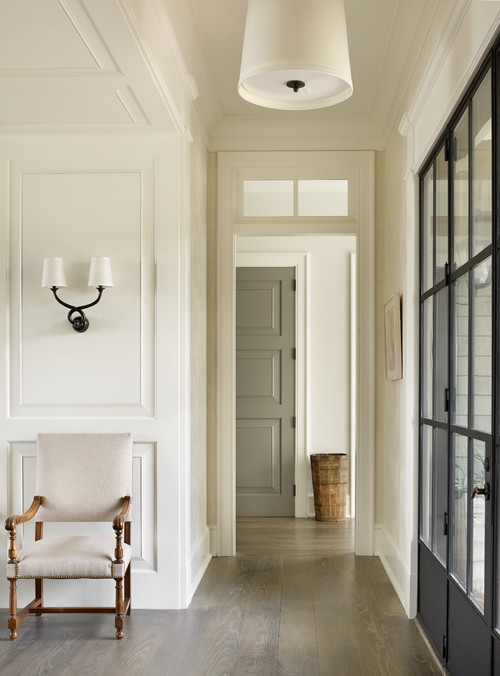 A long hallway with a white chair by the wall and wall sconce above the chair.