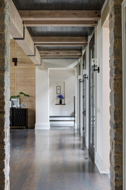 Example of a classic dark wood floor hallway design in Milwaukee with white walls