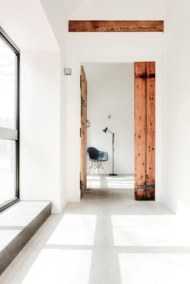 Hallway - scandinavian concrete floor and white floor hallway idea in Hampshire