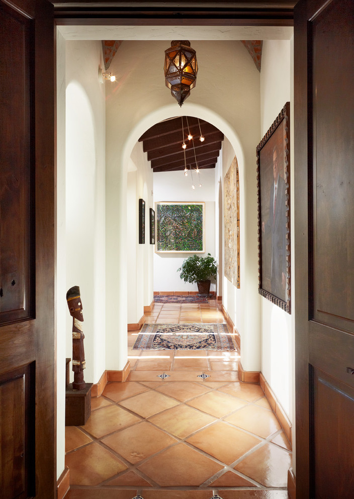 Example of a tuscan terra-cotta tile hallway design in Austin with white walls
