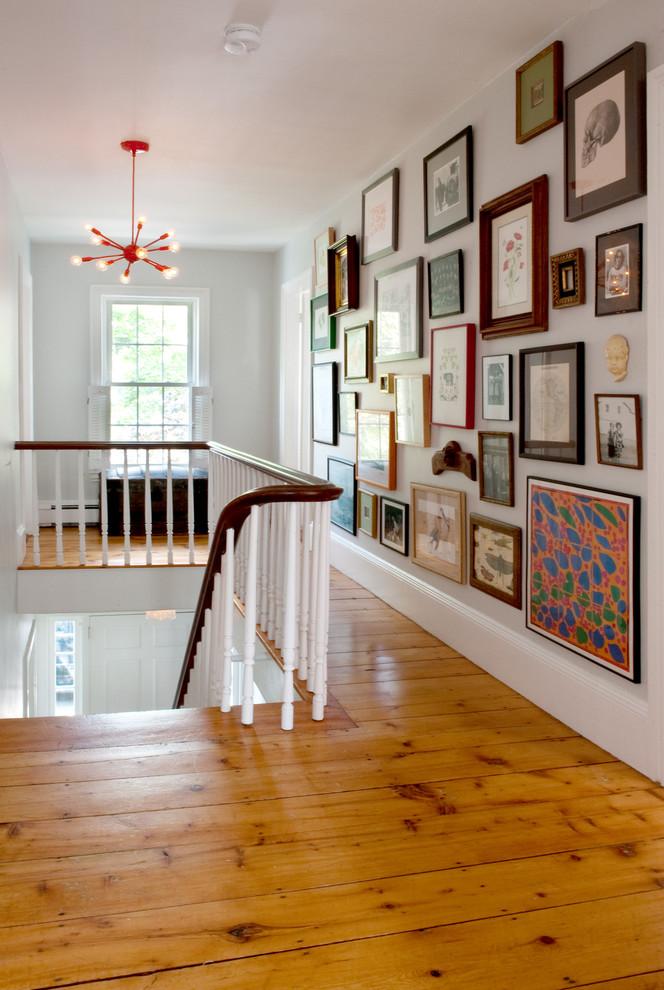Transitional medium tone wood floor hallway photo in Boston with white walls