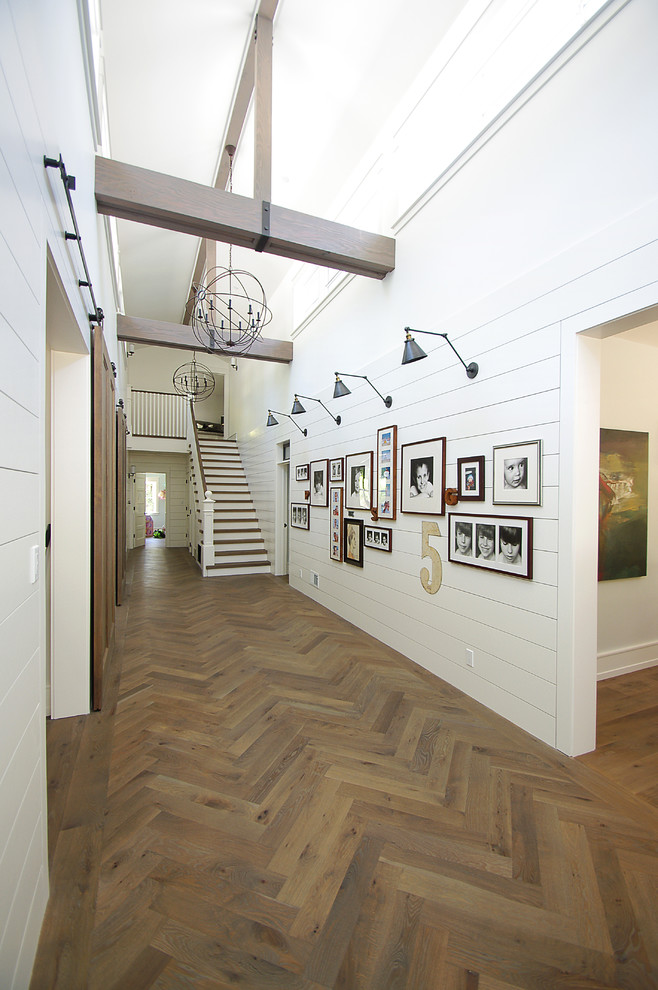 Example of a large country medium tone wood floor and brown floor hallway design in San Francisco with white walls