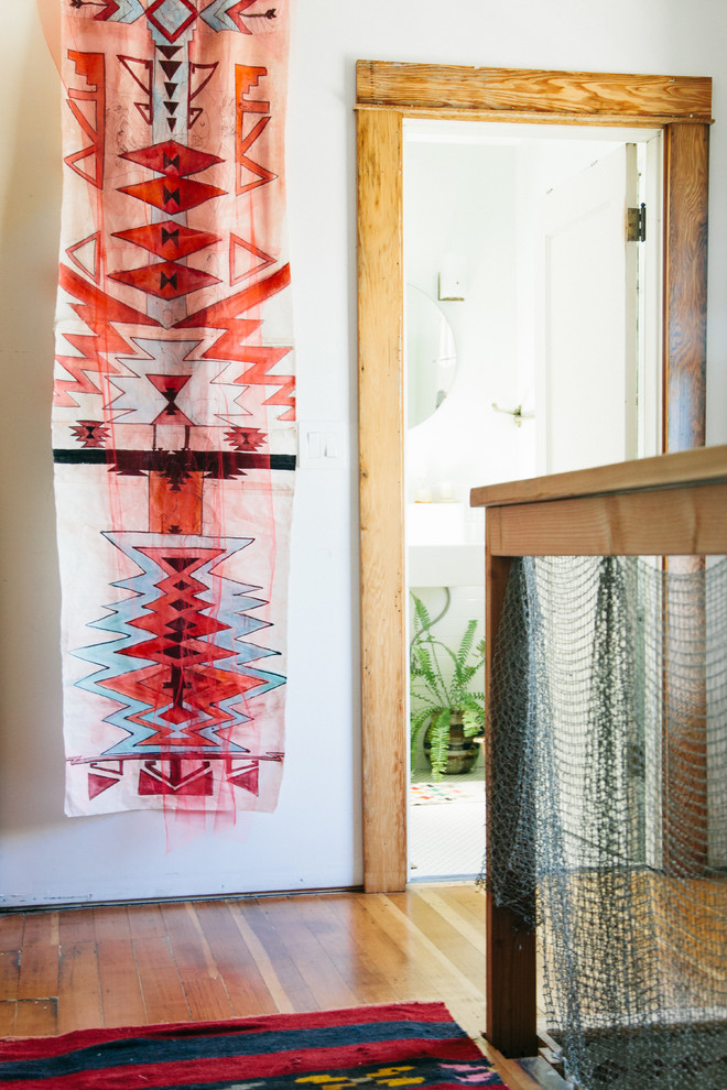 Inspiration for a small eclectic medium tone wood floor hallway remodel in Portland with white walls