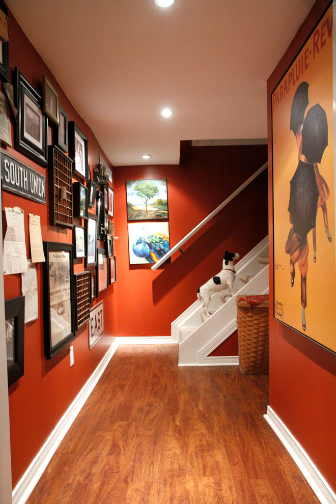 Example of an eclectic dark wood floor and brown floor hallway design in Toronto with red walls
