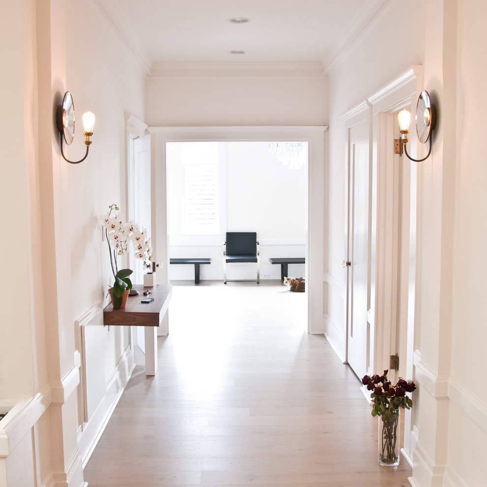 Mid-sized transitional light wood floor hallway photo in San Francisco with white walls