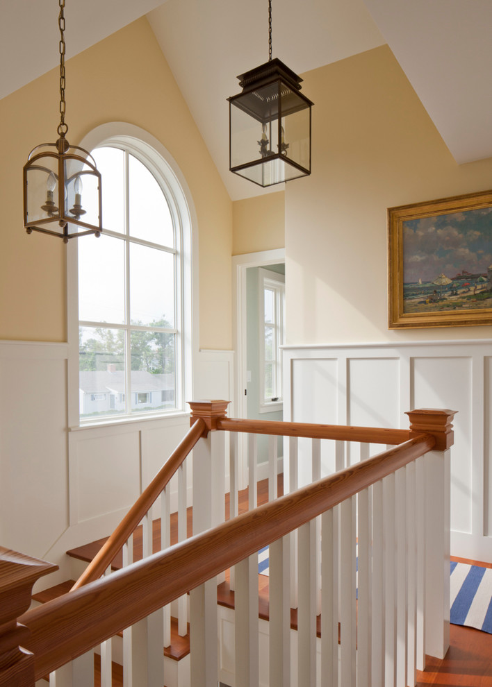 Example of a mid-sized beach style medium tone wood floor and brown floor hallway design in Boston with yellow walls