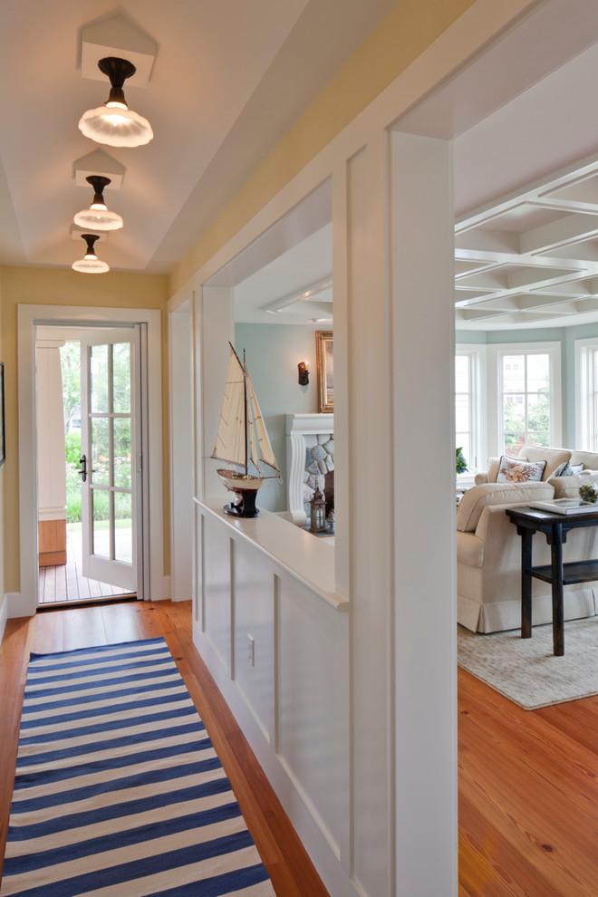 Mid-sized beach style medium tone wood floor and brown floor hallway photo in Boston with beige walls