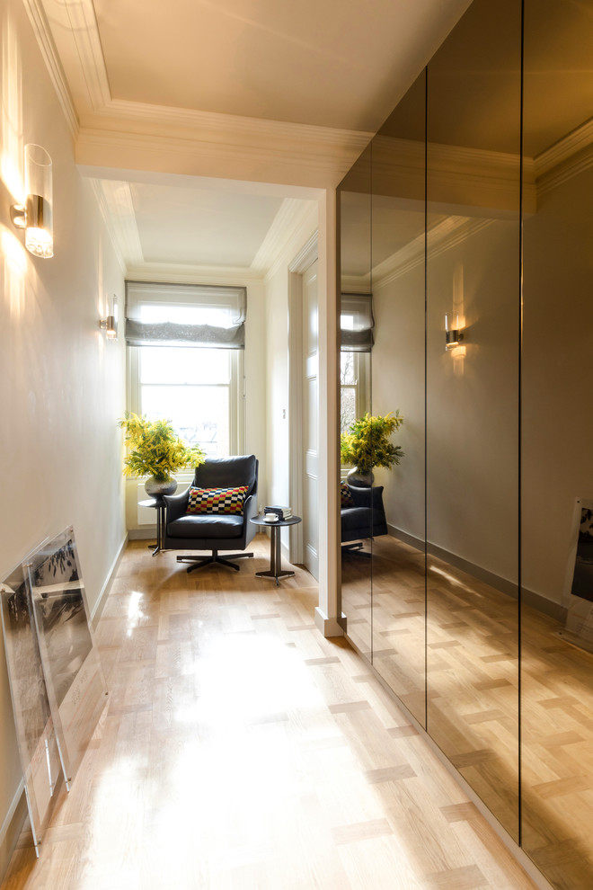 Inspiration for a mid-sized transitional light wood floor and beige floor hallway remodel in London with gray walls