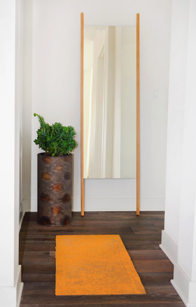 Example of a small trendy medium tone wood floor and gray floor hallway design in Los Angeles with white walls