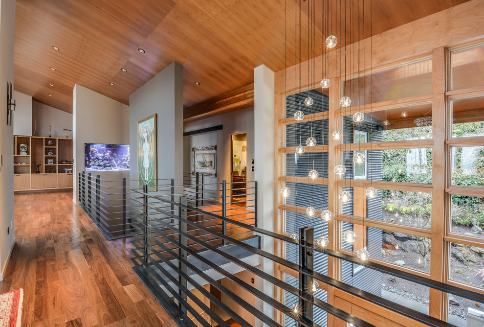 Inspiration for a mid-sized modern medium tone wood floor hallway remodel in Seattle with multicolored walls
