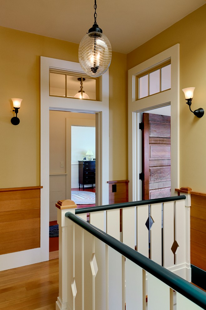 Example of a mountain style medium tone wood floor hallway design in Burlington with beige walls