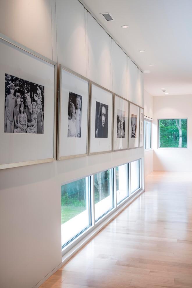 Minimalist light wood floor and beige floor hallway photo in Indianapolis with white walls